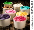 Assorted colorful tubs of fresh dairy ice cream in multiple colors and flavours for a refreshing cold treat on a hot summer day standing on an old wooden table - stock photo