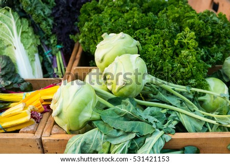 Assorted fresh green vegetables in boxes at a farmers market after harvest