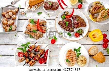 Assorted grilled meats and vegetables on a white wooden table. Healthy eating. View from above