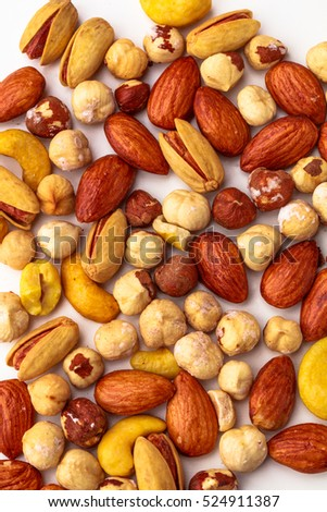 Assorted macadamia, pistachio, almond and cashew nuts spread out on a white background