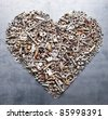 assorted nuts and bolts heart on metal texture background - stock photo