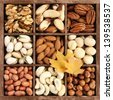 Assorted nuts in a wooden box, with leaves as deco, (manual focus) - stock photo
