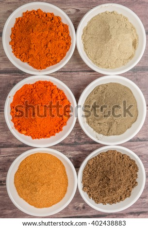 Assortment of hot and spicy chili spices powder in white bowl over wooden background
