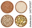 Assortment of seeds in wooden bowls isolated on white - stock photo