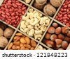 assortment of tasty nuts in  wooden box, isolated on white - stock photo