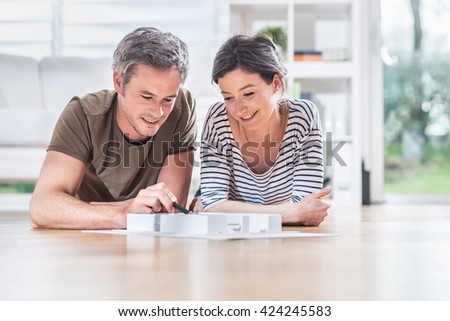 At home, looking at camera, a handsome couple is lying on the wooden floor of the living room. They wear casual clothes, the man is grey haired