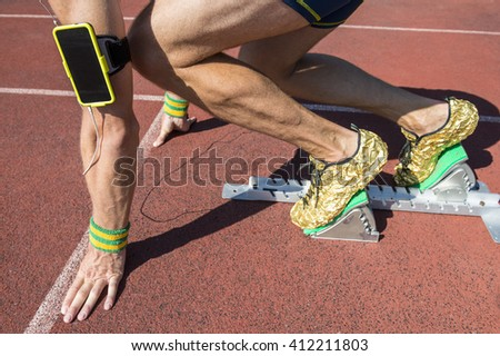 Athlete crouching at the starting line of a running track listening to motivational music on headphones from his mobile phone armband with Brazil colors wristbands