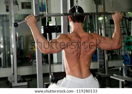 athlete doing fitness training on machine with weights in a gym
