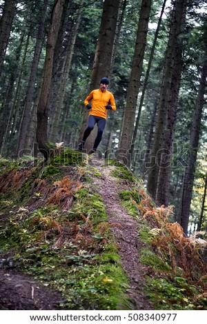 Athlete male runner running downhill in mountain autumn forest