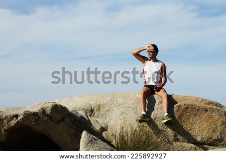 Athlete man in sportswear listening to music on his mobile phone sitting on sea rocks, male runner enjoying the sun and listen to music with headphones, fit man taking break after workout outdoors