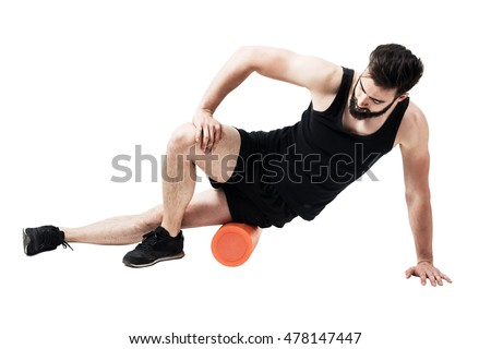 Athlete massaging and stretching iliotibial ban muscle with foam roller. Full body length portrait isolated on white studio background.