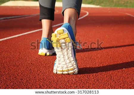 Athlete runner feet down stadium track. Closeup on female shoe and legs. Woman autumn  fitness workout. Jogging, sport, healthy active lifestyle concept.