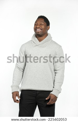 Athletic and attractive black male wearing a fitted gray sweater with black pants in a studio setting on a white background posing and laughing at the camera.