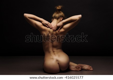 Athletic body of young woman over dark background.