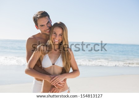Athletic couple smiling at camera at the beach