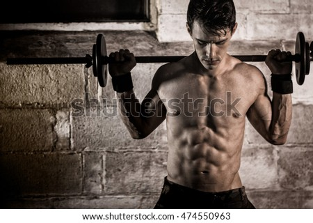 Athletic man exercising with a barbell.