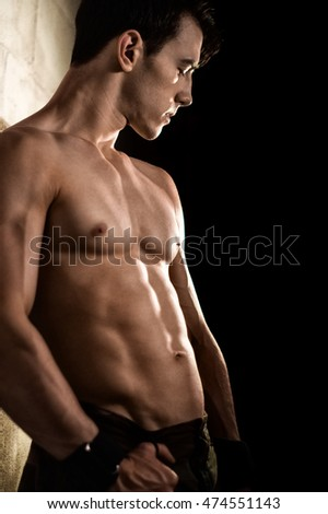 Athletic man posing with flexed muscles against wall.