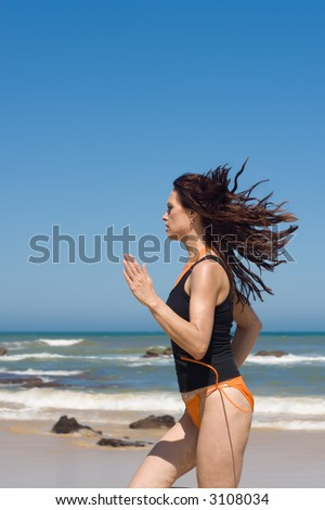 Athletic model running fast on the beach