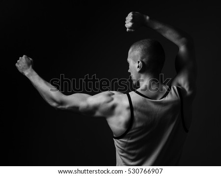 Athletic young man with strong hands. Back view.  Black and white