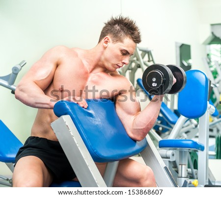 athletically built sportsman doing exercises with dumbbells for the biceps in the gym