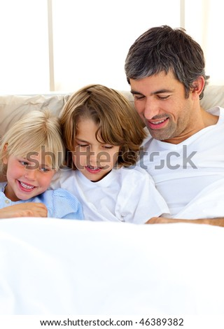 Attentive father and his children reading book lying in bed