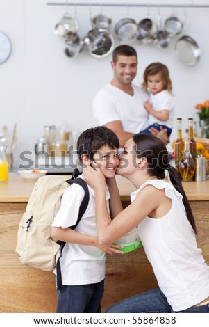 Attentive mother giving school lunch to her son in the kitchen