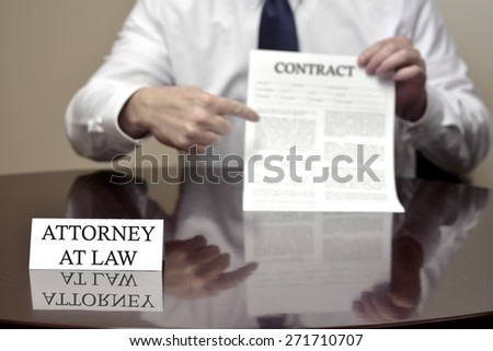 Attorney at Law sitting at desk holding Contract