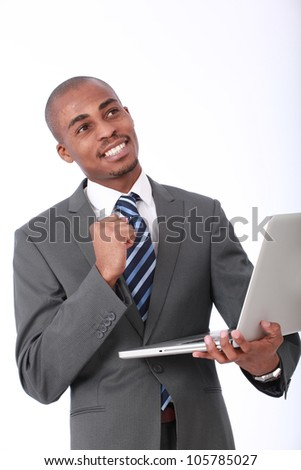 Attractive African American businessman isolated on white wearing corporate gray suit and blue tie holding a laptop computer looking up with a clenched fist punching the air showing success in a deal
