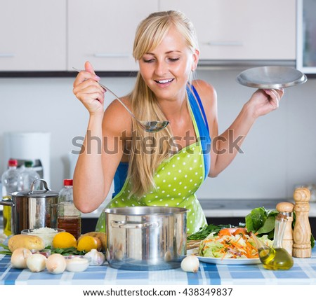 Attractive american girl with long hair cooking vegetables in kitchen