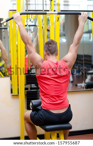 Attractive and fit young man in gym working out and exercising on equipment