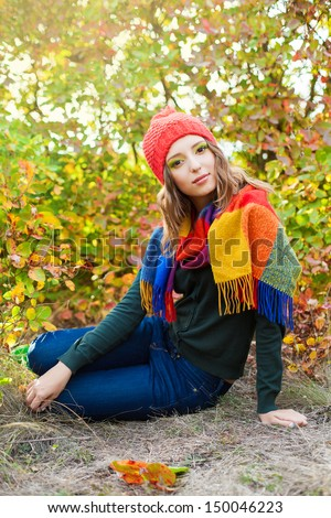 Attractive autumn woman in hat and warm scarf posing outside in colorful fall forest