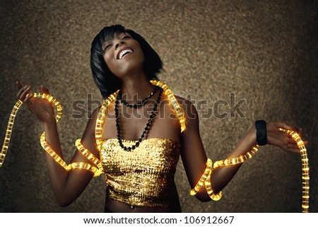 Attractive black woman dancing with Christmas lights around her body, smiling.