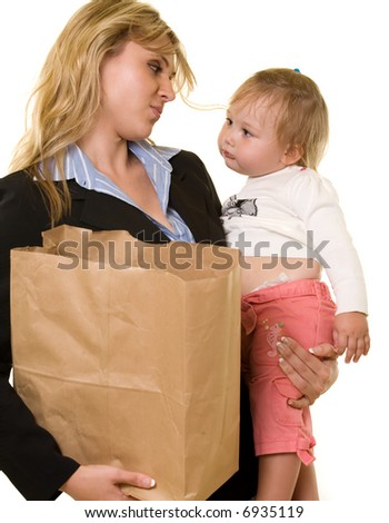 Attractive blond woman in business attire carrying a grocery bag in one arm and baby in the other showing busy mother