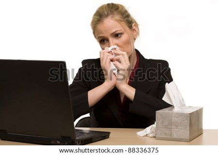 Attractive blond woman secretary sitting at office desk with a box of tissues on the desk while blowing her nose