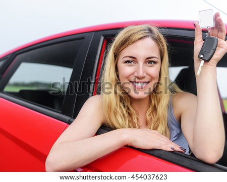 Attractive blonde in a car showing keys.