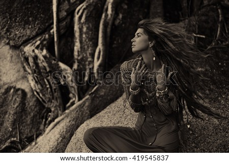 Attractive boho woman sitting on stones outdoors