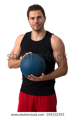 Attractive brunette man in a black tank top and red pants working out with a medicine ball