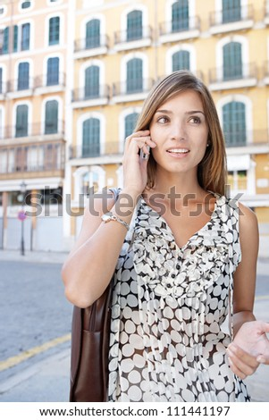 Attractive businesswoman having a conversation on her cell phone in a classic city.