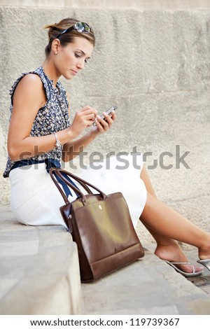 Attractive businesswoman sitting down on stone steps in the city, using a smart phone.