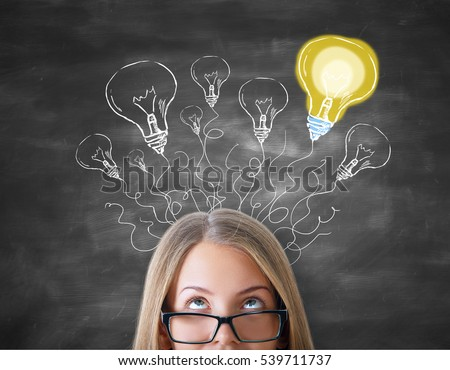 Attractive caucasian girl with abstract light bulb maze on chalkboard background. Creative ideas concept