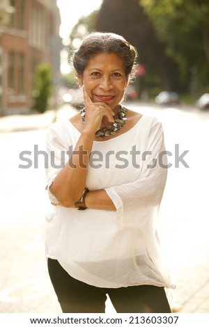 Attractive fashionable middle-aged woman standing in a street looking thoughtfully at the camera with a charming friendly smile