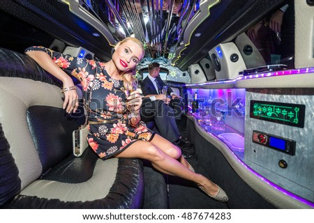 Attractive Female Celebrity With Champagne Flute In Limousine
