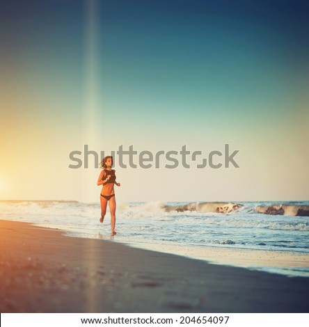 Attractive female runner jogging o the beach touching waves, evening run along the sea, fitness and healthy lifestyle concept