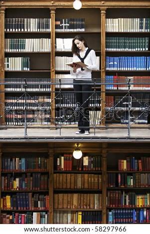 Attractive female student standing in front of bookshelf in old university library reading a book.