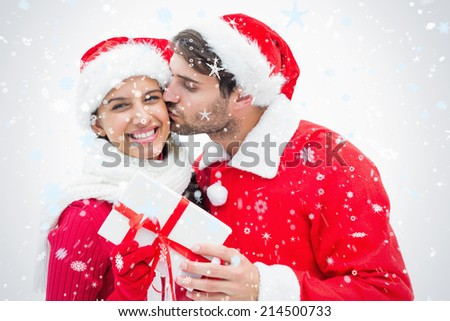 Attractive festive man giving girlfriend a kiss and present against snow falling