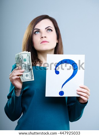 attractive girl in a blue shirt on a gray background holding a question mark and money
