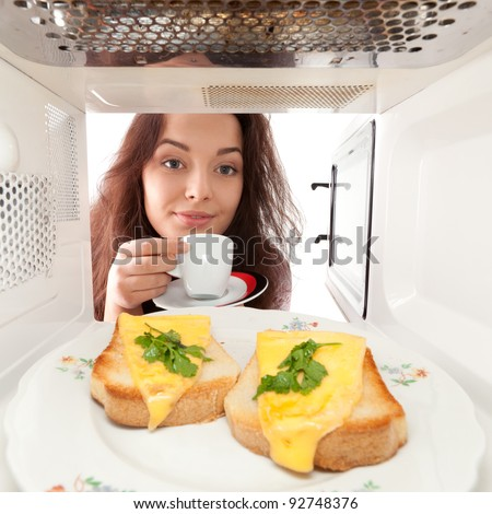 Attractive girl looks in a microwave