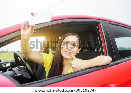 Attractive girl making selfe on the smartphone sitting in the car.