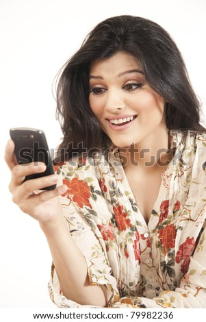 Attractive Indian girl reading or sending an sms