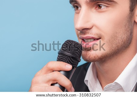Attractive journalist is holding a microphone and speaking into the microphone. The man is smiling and looking aside with joy. Isolated on blue background
